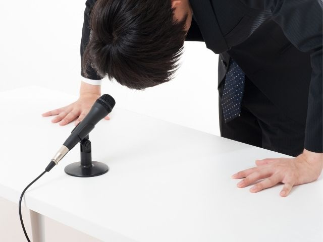 記者会見で謝る男性