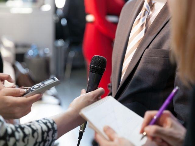 記者から質問される男性